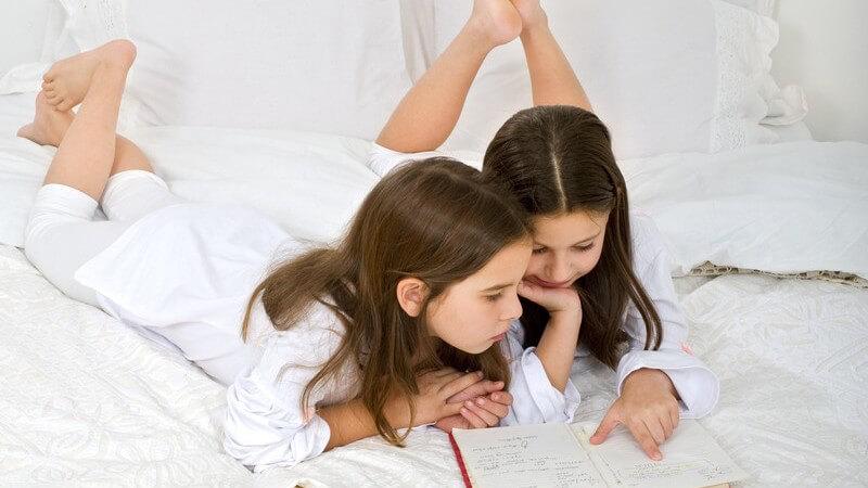 Zwei kleine Mädchen liegen im Bett und lesen ein Buch zusammen