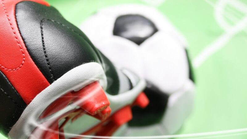 Tritt gegen Fußball, im Hintergrund Grafik Fußballfeld