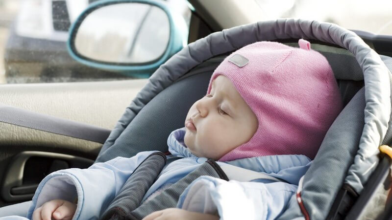 Warm eingepacktes Baby schläft im Kindersitz im Auto