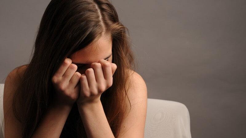 Junge Frau hält Hände vor Gesicht, Trauer, Einsamkeit