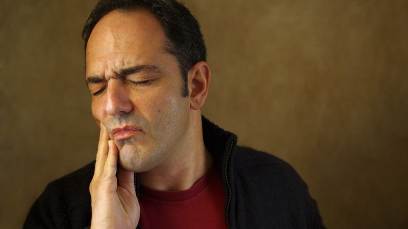Brünetter Mann mit hoher Stirn hält sich mit der Hand den Kiefer und verzieht schmerzvoll das Gesicht