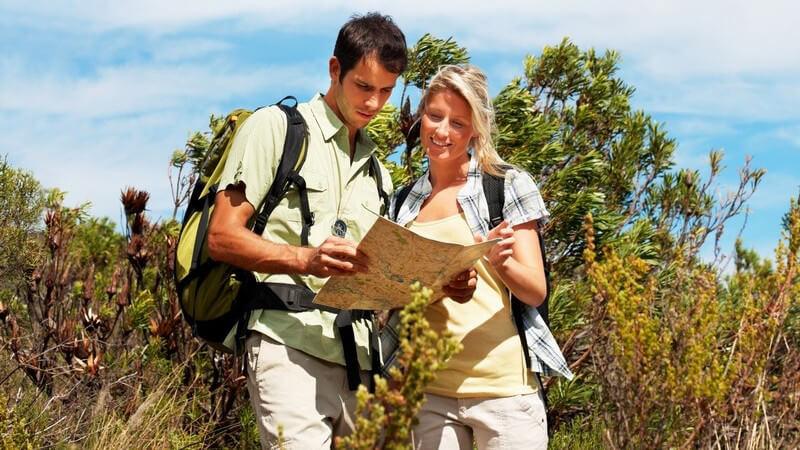Junges Paar in Natur mit Rucksäcken schaut auf Karte