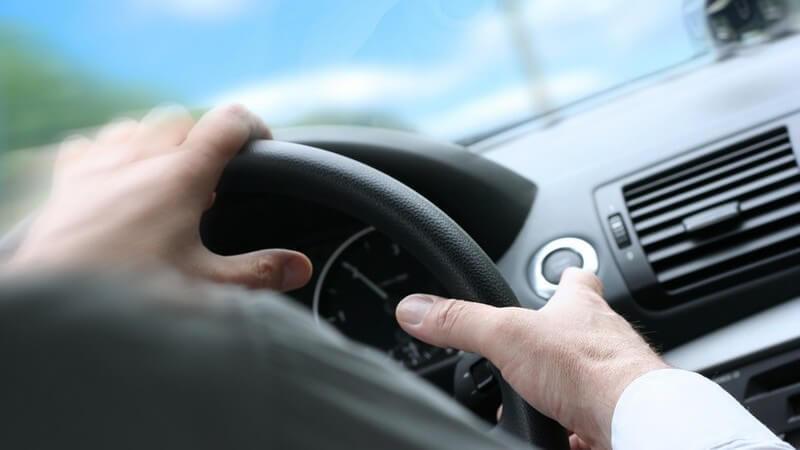 Hände eines Geschäftsmanns am Lenkrad beim Autofahren
