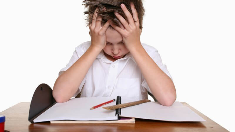Junge hält verzweifelt Kopf in den Händen über Hausaufgaben