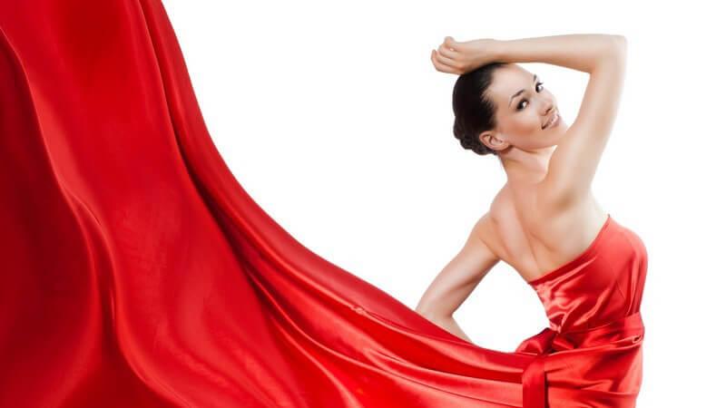 Frau im schulterfreien, langen roten Kleid aus Seide
