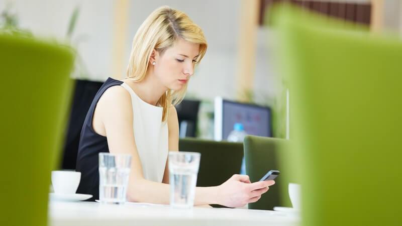 Geschäftsfrau sitzt am Tisch eines Büros und bedient ihr Smartphone