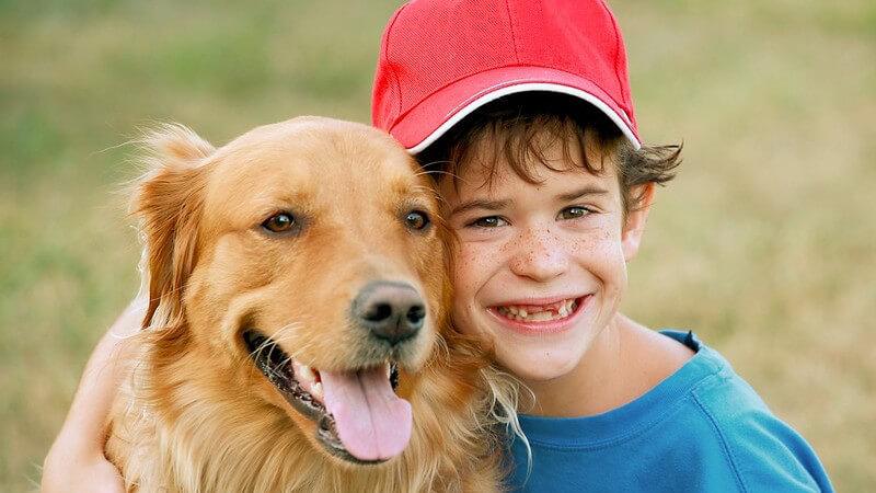 Junge umarmt seinen Hund, Golden Retriever