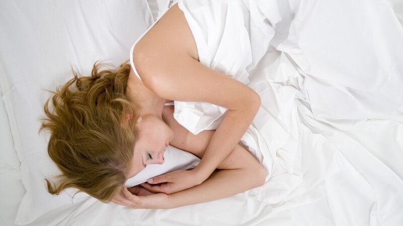 Blonde Frau liegt schlafend auf der Seite in weißen Laken, von oben fotografiert