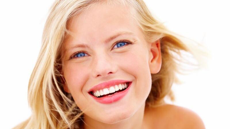 Glückliche, lachende Frau schaut in Kamera, weißer Hintergrund