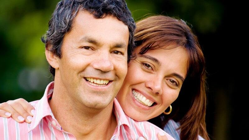 Mann und Frau, sie steht hinter ihm und hält ihn an Schultern fest