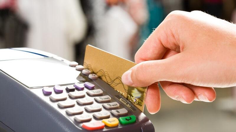 Frau an Kasse zieht EC-Karte durch Scanner