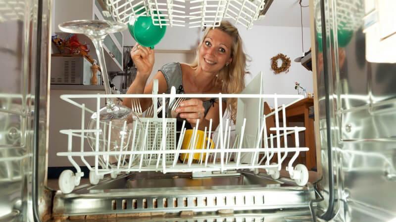 Junge Frau schaut in Geschirrspüler, hält Geschirr und lächelt