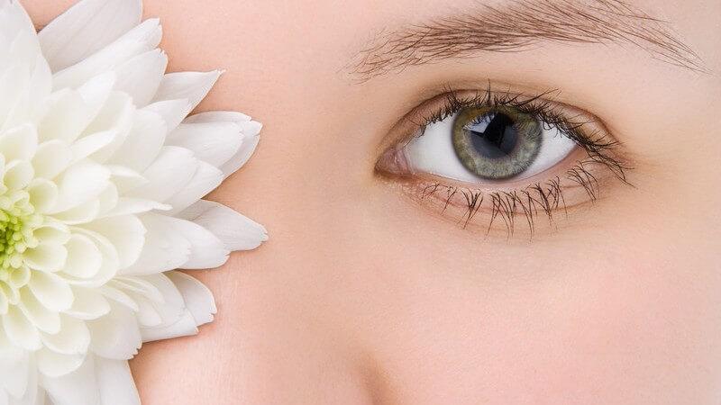 Gesicht einer jungen Frau mit weißer Chrysantheme vor dem rechten Auge