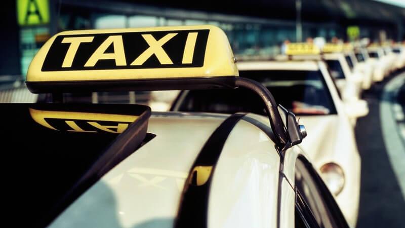 Nahaufnahme Schild eines Taxis, im Hintergrund lange Reihe aus Taxis am Flughafen