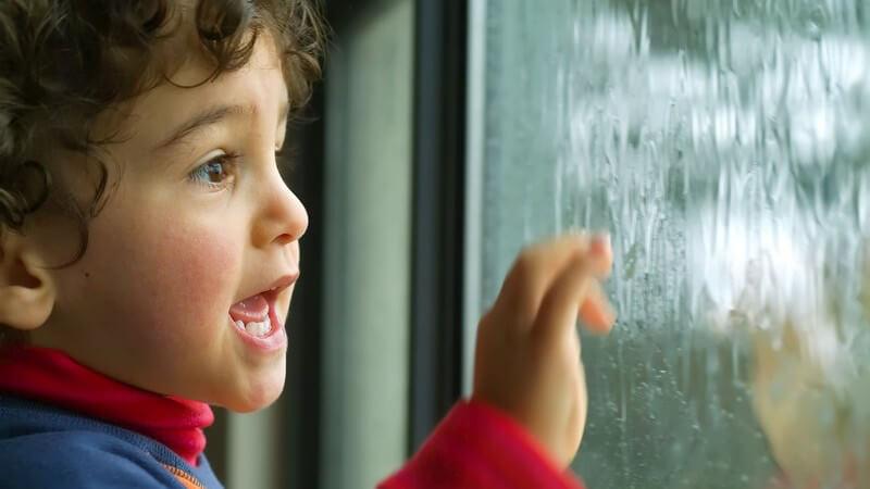 Kleiner Junge steht am Fenster und schaut dem Regen zu