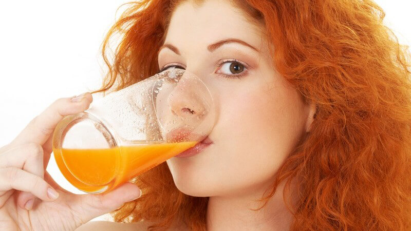 Junge rothaarige Frau trinkt Orangensaft