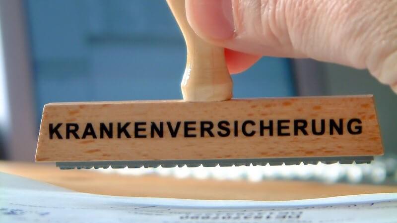 """Holzstempel mit Schriftzug """"Krankenversicherung"""" wird benutzt"""
