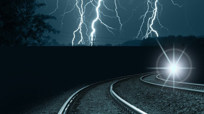 Eisenbahnschienen bei Nacht, Blitze am dunklen Himmel