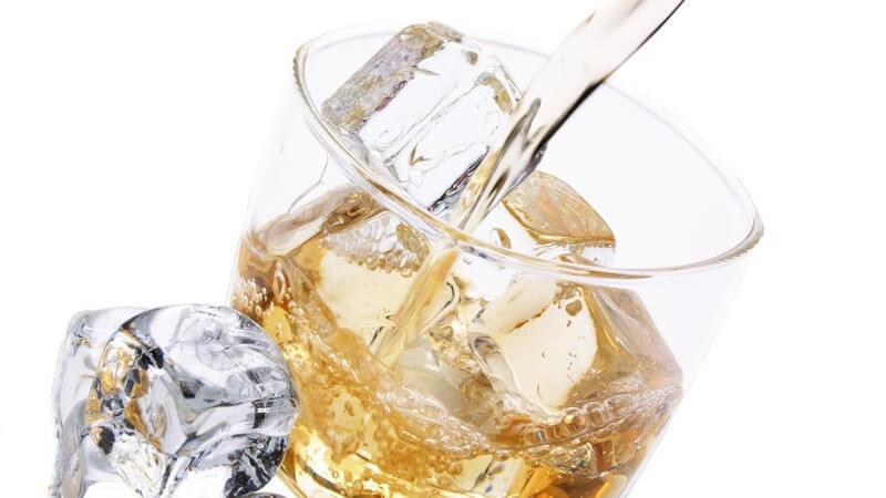 Nahaufnahme alkoholisches Getränk wird in Glas mit Eiswürfeln geschüttet