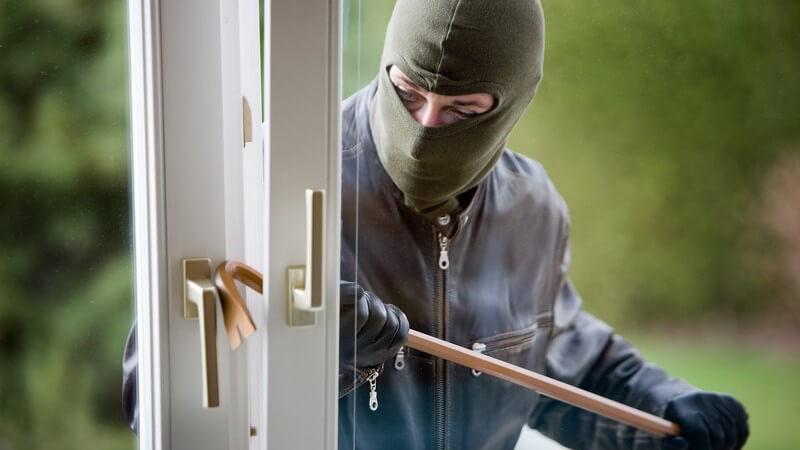 Maskierter Einbrecher versucht mit Brecheisen gekipptes Fenster zu öffnen