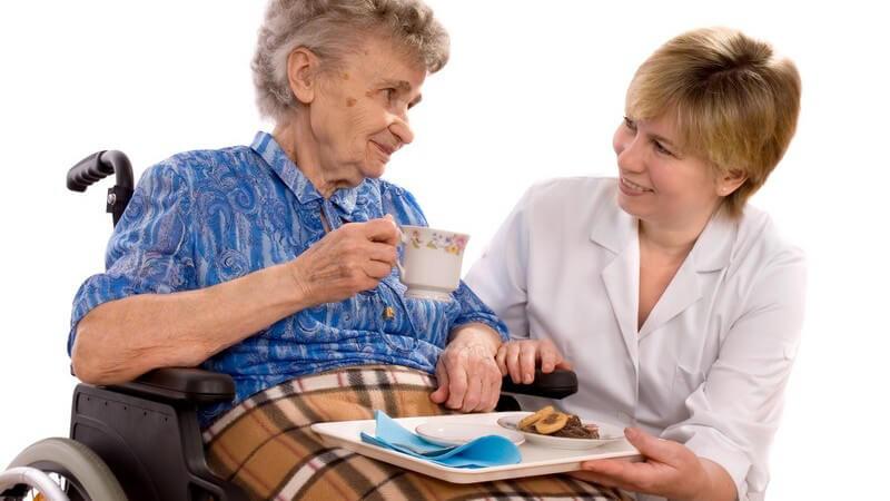 Pflegerin betreut alte Frau im Rollstuhl