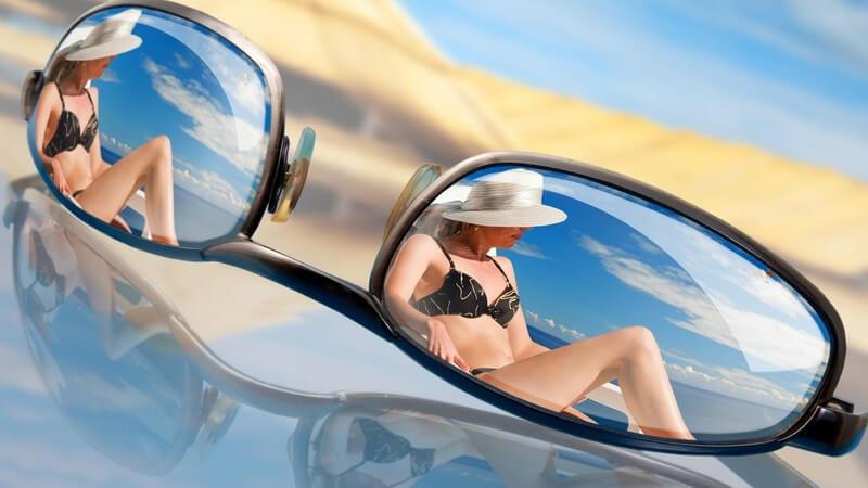 Nahaufnahme Sonnenbrille auf Glastisch, darin spiegelt sich Frau im Bikini