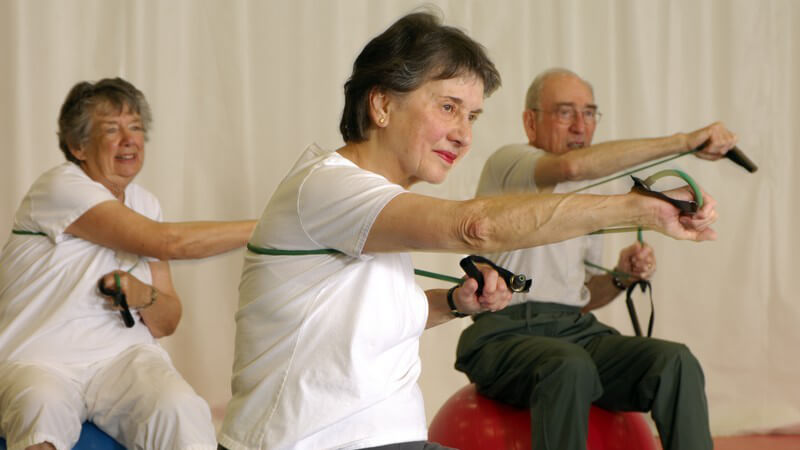 Senioren auf Gymnastikbällen bei Fitnessübungen