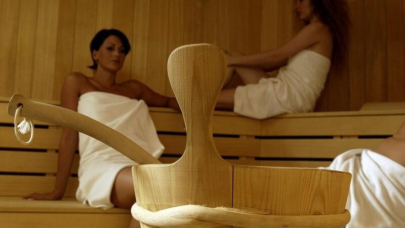 Zwei Frauen in weißen Handtüchern sitzen in Sauna, im Vordergrund Aufguss Gefäß