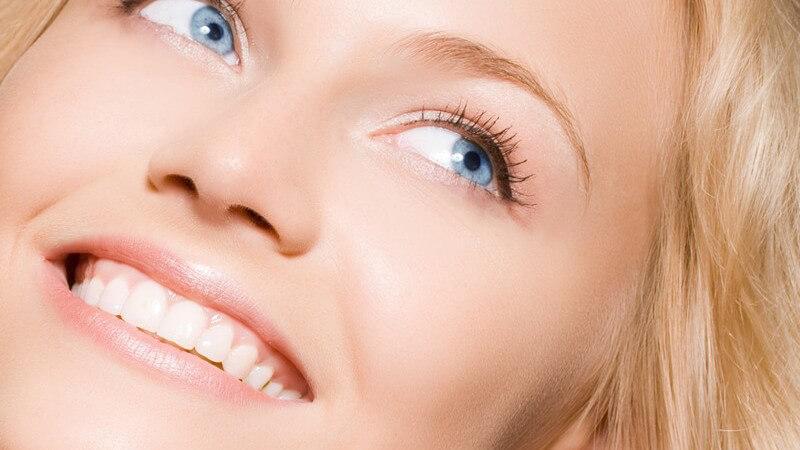 Blonde, lachende Frau mit blauen Augen schaut über ihre Schulter nach oben