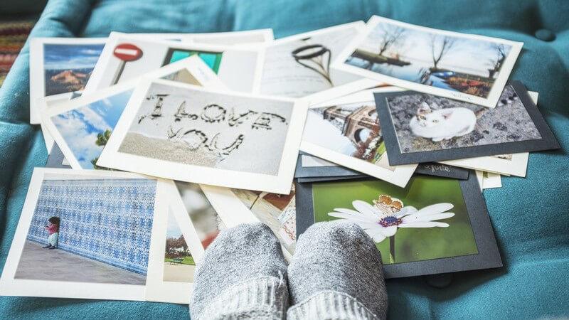 Postkarten liegen verstreut auf einer türkisfarbenen Couch