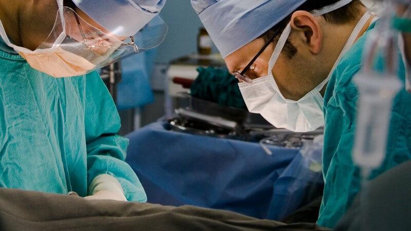 Operation - Zwei Chirurgen mit grünem Kittel und blauer Haube beim Operieren