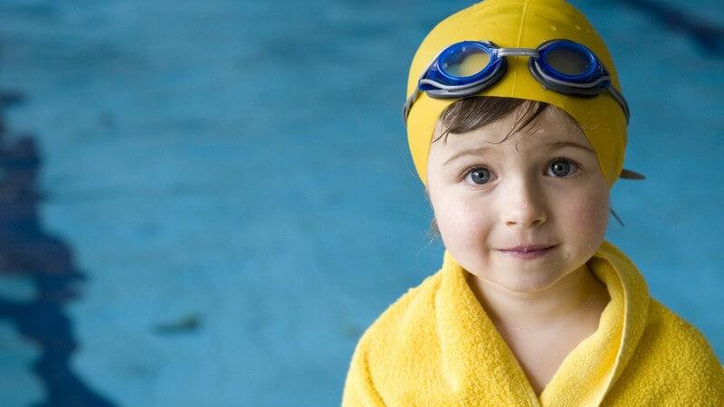 Kleines Mädchen mit Schwimmkappe, Handtuch und Taucherbrille vor Schwimmbecken