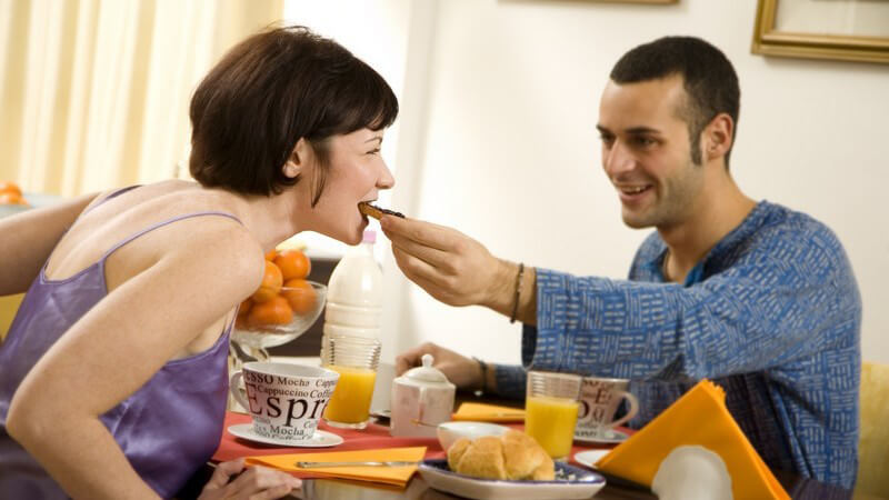 Dunkelhaarige junge Frau und junger Mann, Pärchen, am Frühstückstisch, Mann füttert Frau