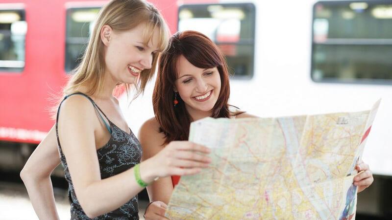 Zwei junge Frauen schauen am Bahnhof auf Stadtplan, im Hintergrund Zug