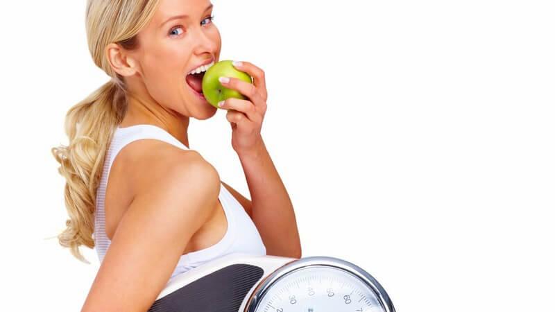 Junge Frau beisst in grünen Apfel, trägt Waage
