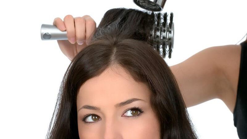 Friseur föhnt lange dunkle Haare einer Frau über Rundbürste