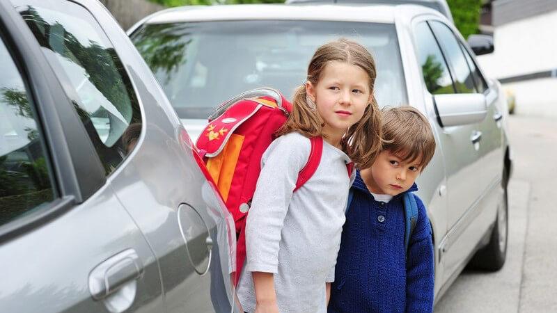 Zwei Kinder auf dem Schulweg, schauen ob Autos kommen, bevor sie Straße überqueren