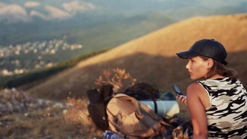 Junge Frau mit Kappe sitzt mit Wanderrucksack in einsamer Berglandschaft