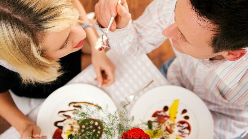Paar von oben fotografiert, er füttert sie mit Dessert