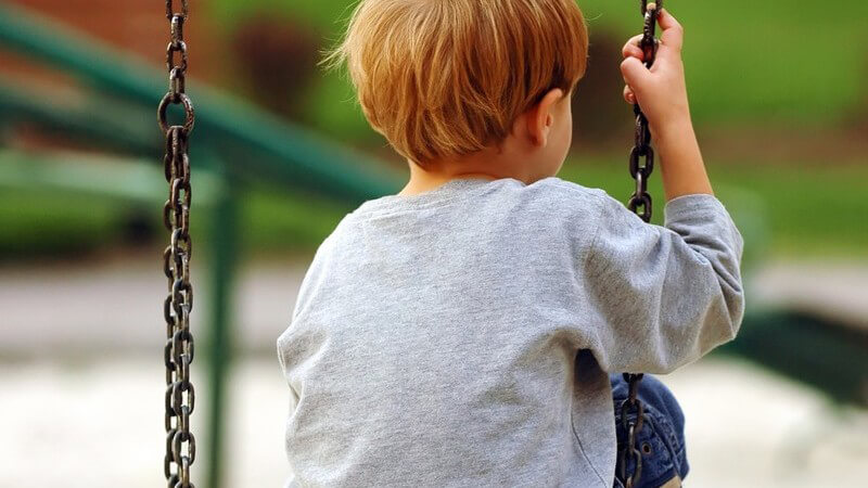 Rückansicht eines kleinen, blonden Jungen auf einer Schaukel