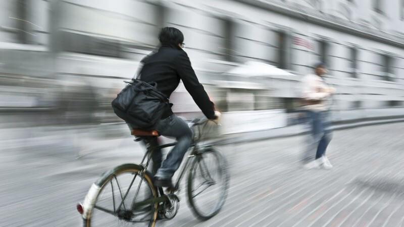 Fahrradfahrer in der Stadt fährt entlang einer Häuserwand
