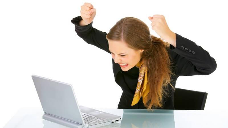Geschäftsfrau sitzt am Laptop und hält frustriert die Fäuste in die Luft
