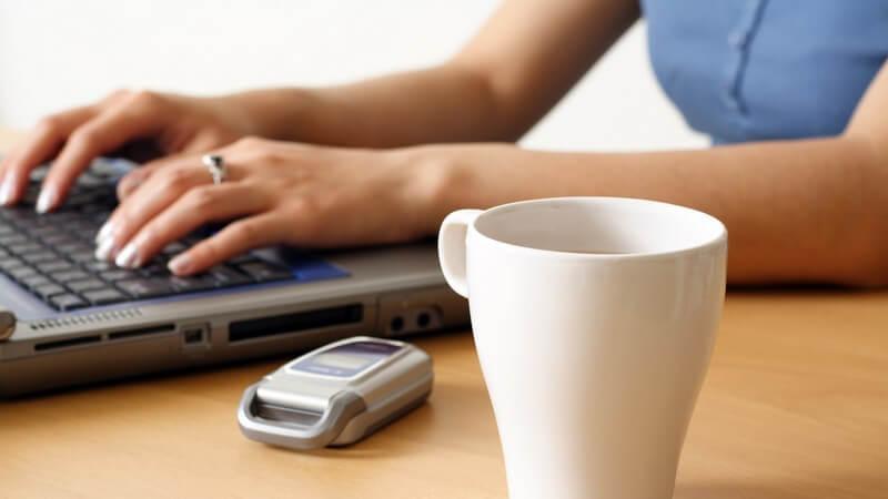 Hände einer Frau auf Notebook Tastatur, daneben Becher Kaffee und Handy