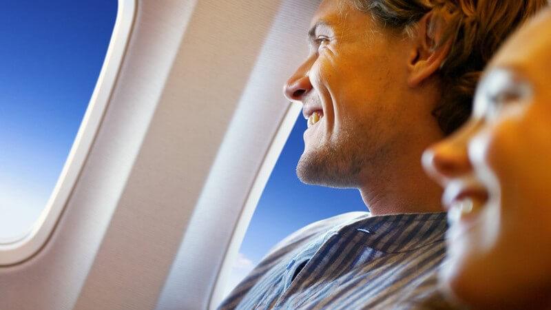 Junger lächelnder Mann auf Fensterplatz in Flugzeug, neben ihm lächelnde junge Frau