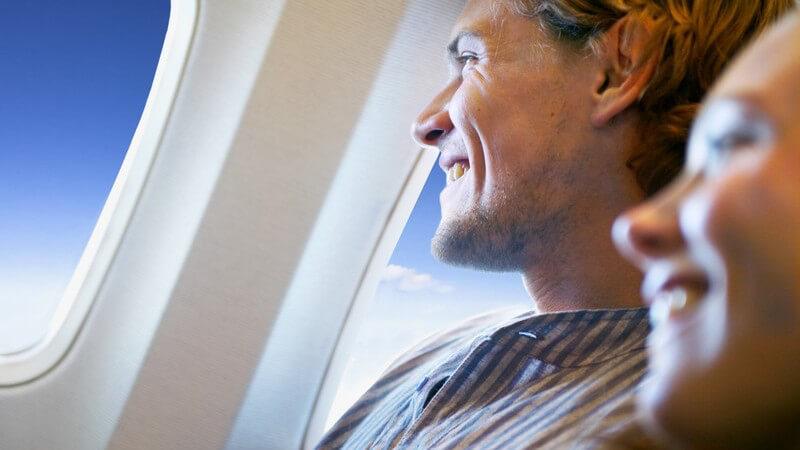 Junger Mann auf Fenstersitz in Flugzeug, schaut aus dem Fenster in den Himmel, junge lächelnde Frau unscharf daneben