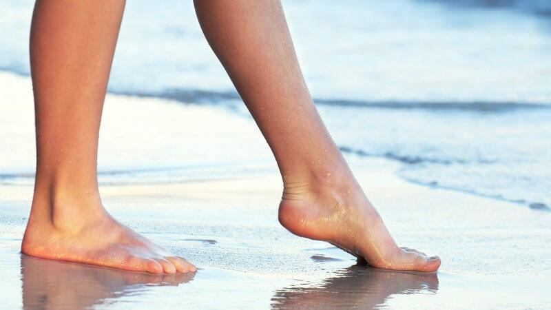 Frauenbeine am Wasser, Frau geht mit nackten Füße am Strand spazieren