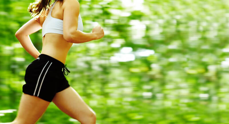 Körperausschnit Frau joggt im Sportoutfit im Wald