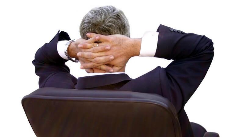 Rückenansicht Geschäftsmann im Bürostuhl, Hände im Nacken gekreuzt