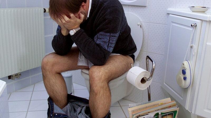 Mann sitzt im Bad auf Toilette, Gesicht in Hände gestützt, Durchfall