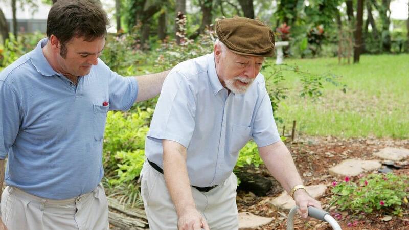 Alter Mann mit braunem Hut und Rollator, junger Mann fasst ihm an den Rücken im Park